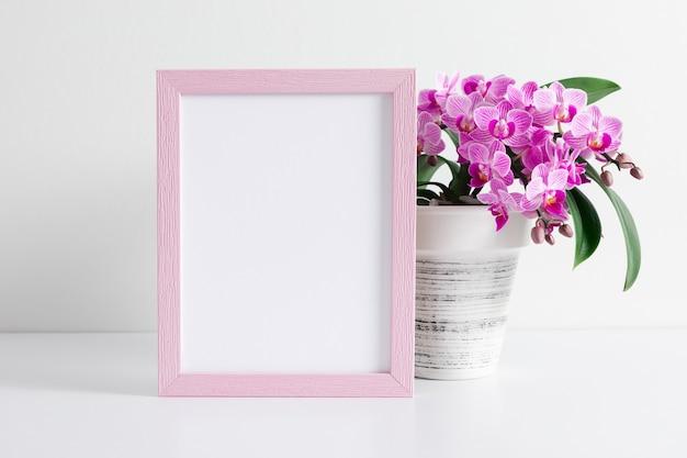 Postermodell oder bilderrahmen mit rosa orchideenblüten auf weißem tisch