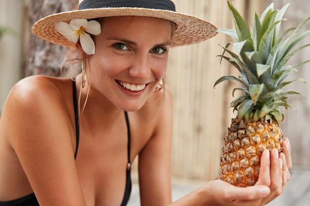 Postive entzückende frau in badebekleidung und hut, genießt sommerzeit, verbringt urlaub im tropischen land, hält ananas, isst obst, um gesund und fit auszusehen. hübsche frau mit exotischen leckeren früchten