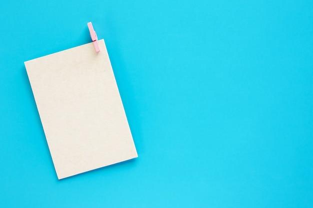 Postkarte des leeren papiers mit hölzernem pflock auf blauem hintergrund