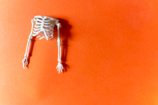 Postkarte für menschliches skelett von halloween auf einem orangefarbenen hintergrund flach mit kopienraum