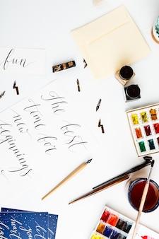 Postkarte mit kalligraphietintenpinseln aquarellfarben über weißer wand