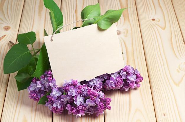 Postkarte mit violetten lila blumen auf holztisch