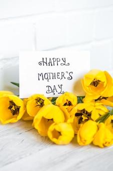 Postkarte muttertag und gelbe tulpen auf einem hellen hölzernen hintergrund, feiertagskonzept