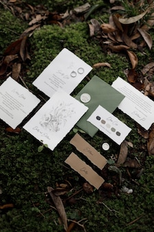 Postkarten-umschlag und karte auf hochzeitsdruck auf dem hintergrund mit gras und moos