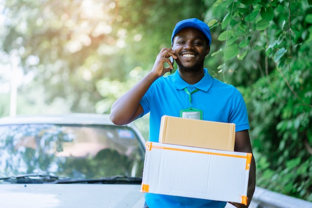 Postkuriermann des lächelns afrikanischer vor dem auto, das paket mit unterhaltungs-smartphone liefert.