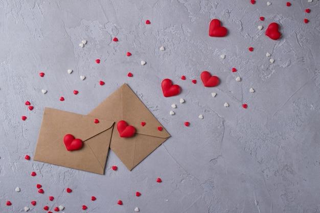 Postumschlag mit zwei kraftpapieren mit süßen zuckersüßigkeitsmehrfarbenherzen. liebesmitteilung oder geschenkkonzept.