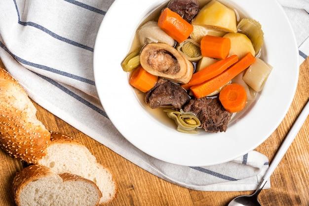Pot-au-feu beliebte warme gerichte der traditionellen französischen küche. gedünstetes rindfleisch und gemüse mit rinderbrühe in einer weißen platte auf einem holztisch. warme wintermahlzeit.