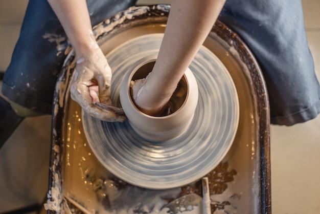 Potter arbeitet an einem potterrad und baut eine vase