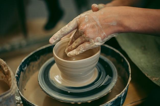 Potter stellt mit seinen händen einen tonkrug her