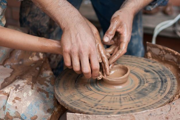 Potter unterrichtet das modellieren im tontopf auf einer sich drehenden töpferscheibe