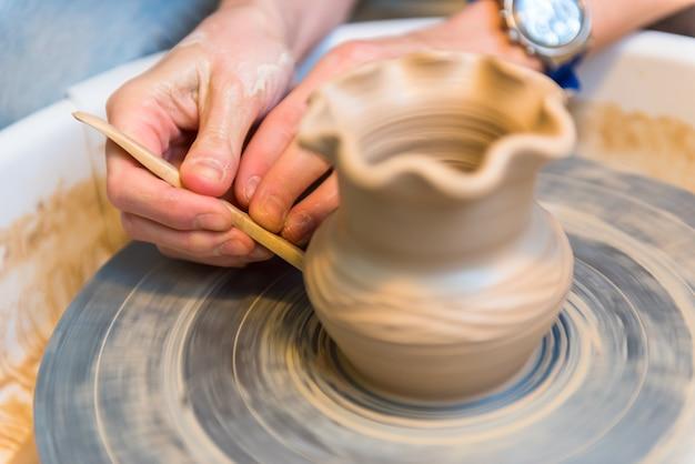 Pottering - erstellen eines tonbechers in bearbeitung. mit einem kleinen griff geschossen