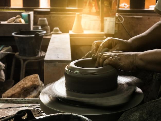 Potters hände formen weichen ton zu einem irdenen topf