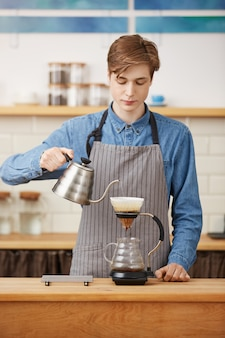 Pouron kaffee machen. netter barista, der kaffeegetränk bereitet und konzentriert aussieht.