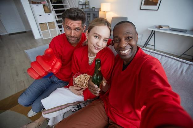 Pov-ansicht auf eine gruppe von sportfans, die rot tragen und selfies machen, während sie das spiel zu hause ansehen
