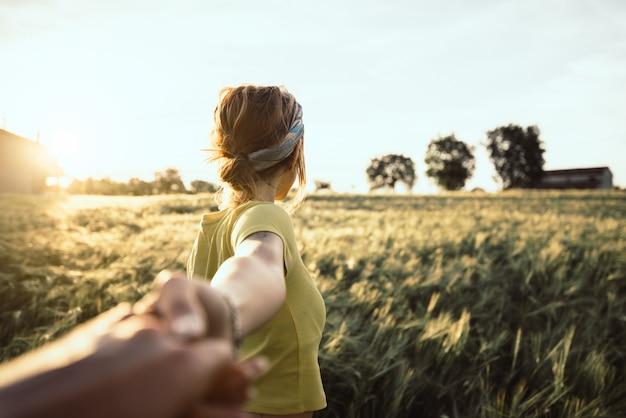Pov ansicht einer glücklichen jungen frau, die hand ihres freundes beim gehen durch ein weizenfeld bei sonnenuntergang hält. paar genießt reisen in der natur
