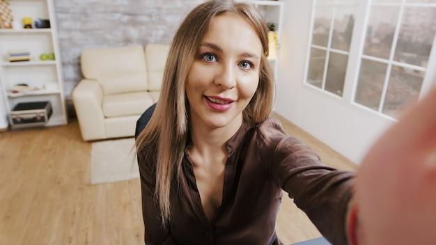 Pov-aufnahme einer modeinfluencerin, die einen vlog für ihre abonnenten aufzeichnet. schöne maskenbildnerin.