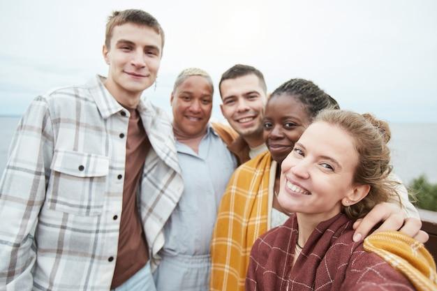 Pov-aufnahme einer verschiedenen gruppe junger freunde, die während der wanderung ein selfie am aussichtspunkt machen