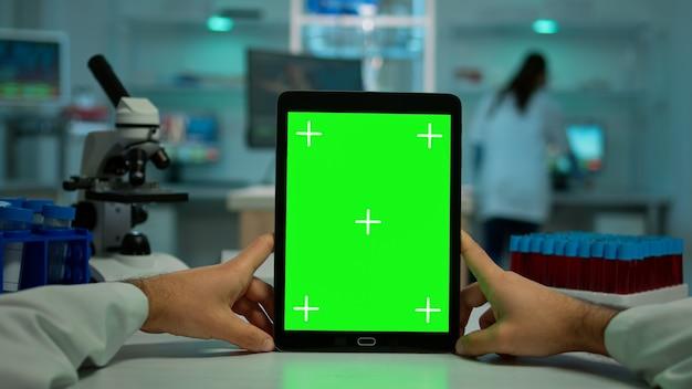 Pov-aufnahme eines chemikers mit tablet mit grünem bildschirm im biologischen labor. medizinischer arbeiter mit weißem kittel in der klinik, der mit notebook mit chroma-key auf isoliertem display im medizinischen labor arbeitet