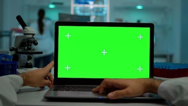 Pov-aufnahme eines mikrobiologen, der auf einem laptop mit grüner chroma-key-anzeige tippt, der am schreibtisch sitzt und virussymptome liest. im hintergrund laborforscher, die impfstoffentwicklung untersuchen, untersuchen proben