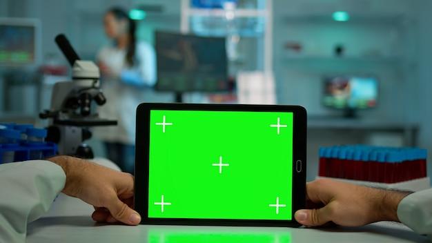 Pov-aufnahme eines mikrobiologen, der ein tablet mit grüner chroma-key-anzeige hält und am schreibtisch sitzt und virussymptome liest. im hintergrund laborforscher, die impfstoffentwicklung untersuchen, untersuchen proben
