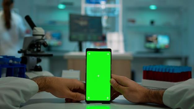 Pov-aufnahme eines mikrobiologen, der ein telefon mit grünem chroma-key-display hält, das am schreibtisch sitzt, sucht und virussymptome liest. im hintergrund laborforscher, die impfstoffentwicklung untersuchen, untersuchen proben