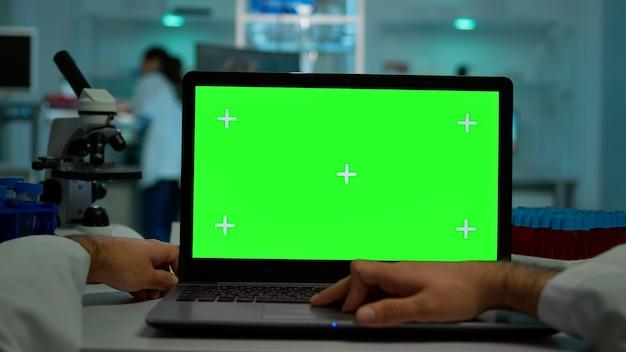 Pov-aufnahme eines wissenschaftlers, der am schreibtisch sitzt und an einem laptop mit grünem mock-up-bildschirm arbeitet, isolierte anzeige. im hintergrund laborforscher, die impfstoffentwicklung untersuchen, untersuchen proben