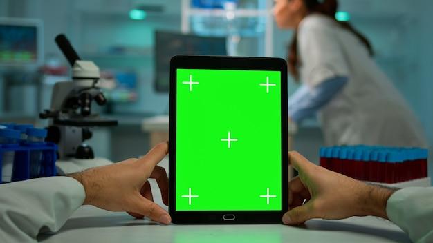 Pov-aufnahme eines wissenschaftlers, der am schreibtisch sitzt und an einem notebook mit grünem mock-up-bildschirm arbeitet, isolierte anzeige. im hintergrund laborforscher, die impfstoffentwicklung untersuchen, untersuchen proben