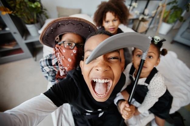 Pov-aufnahme von aufgeregten afroamerikanischen kindern, die an halloween selfies machen, während sie kostüme tragen