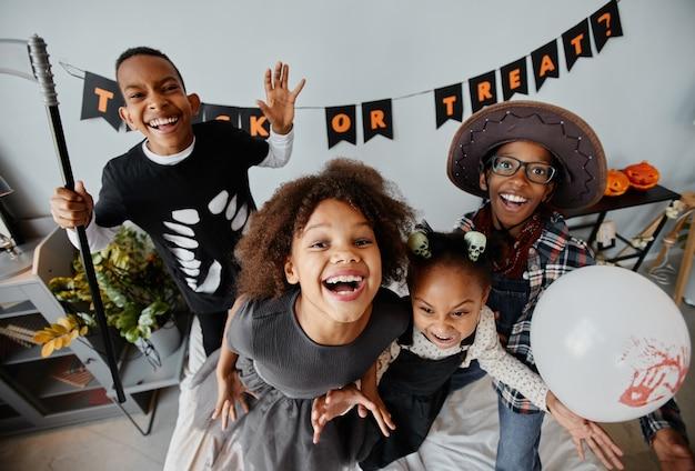 Pov-aufnahme von aufgeregten afroamerikanischen kindern, die zu hause halloween-kostüme tragen und in die kamera schauen