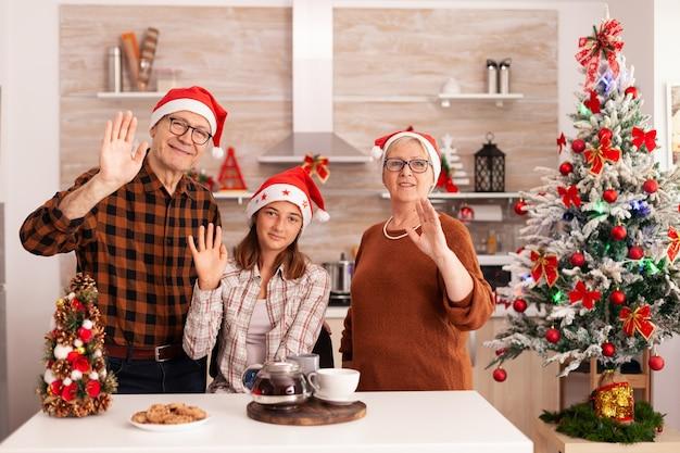 Pov der familie mit weihnachtsmützen, die freunde während des online-videoanrufs begrüßen