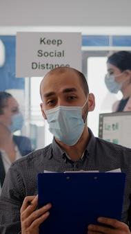 Pov des geschäftsmannes in der gesichtsmaske, um eine infektion zu vermeiden, die auf einer online-videoanrufkonferenz während eines zoom-meetings spricht. unternehmerarbeitssicherheit im neuen normalen büro