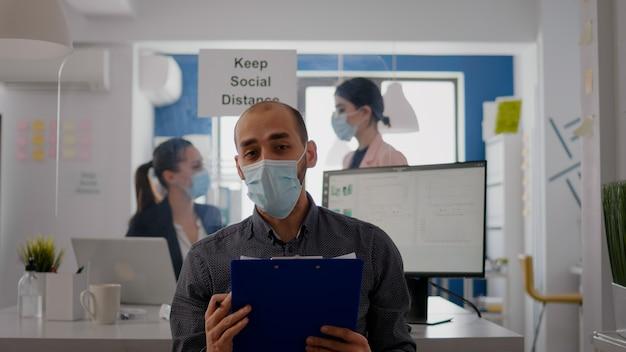 Pov des geschäftsmannes in gesichtsmaske, um eine infektion zu vermeiden, die auf einer online-videoanrufkonferenz während eines zoom-meetings spricht. unternehmerarbeitssicherheit im neuen normalen büro