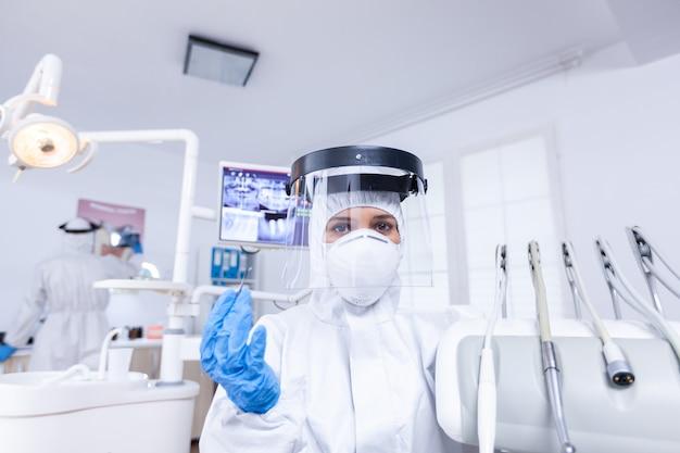 Pov des patienten, der auf dem stuhl in der zahnarztpraxis für die zahnbehandlung sitzt stomatolog, der während der gesundheitsprüfung des patienten sicherheitsausrüstung gegen coronavirus trägt.