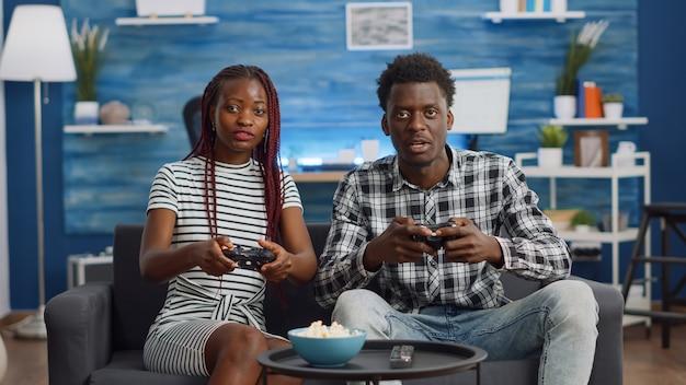 Pov des schwarzen paares, das videospiel mit controller spielt
