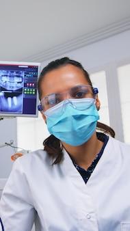 Pov des zahnarztes, der an der mundhygiene des patienten in der zahnarztpraxis arbeitet und zahnprobleme überprüft. arzt untersucht im kieferorthopädischen büro mit lichtlampe und sterilisierten utensilien, nahaufnahme gesicht in medizinischer maske.