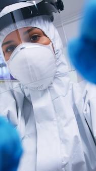 Pov des zahnarztes in ppe-klage gegen covid, der an der mundhygiene des patienten in der zahnarztpraxis mit neuer normalität arbeitet. stomatolog, der während der gesundheitsprüfung des patienten sicherheitsausrüstung gegen coronavirus trägt.