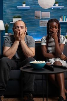 Pov eines interracial paares, das schockiert ist, einen dramafilm im fernsehen im wohnzimmer anzusehen. gemischte rassenpartner mit händen über dem mund, die kamera und fernsehen betrachten. multiethnische liebhaber