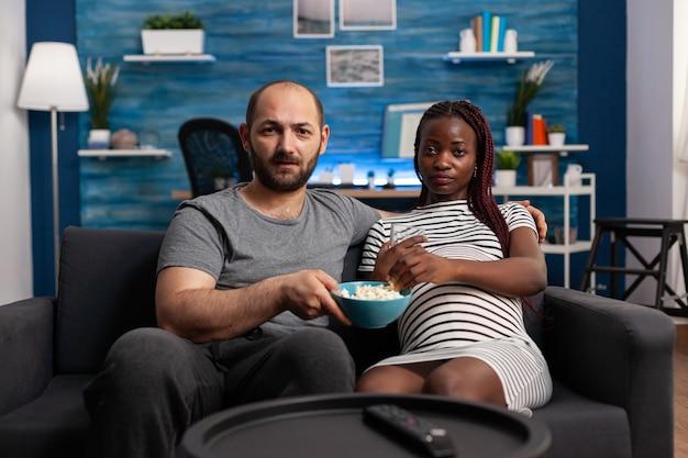 Pov eines interracial paares mit schwangerschaft, das im wohnzimmer einen film im fernsehen sieht. multiethnischer mann und schwangere frau, die ein baby erwarten und in die kamera schauen, während sie popcorn und wasser haben