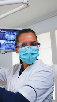 Pov eines patienten in einer zahnklinik, der auf einem operationsstuhl sitzt und die betroffene masse überprüft. zahnärzteteam, das in der kieferorthopädischen praxis arbeitet, die lampe anzündet und die person untersucht, nahaufnahme des gesichts in medizinischer maske.