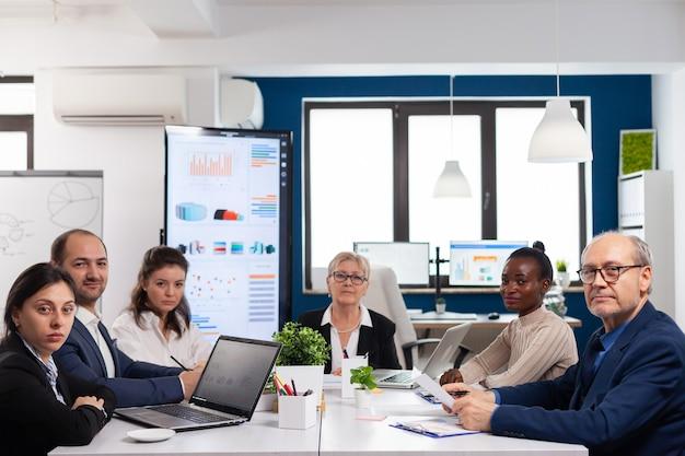 Pov eines vielfältigen teams, das während eines virtuellen meetings im konferenzraum sitzt und online mit geschäftspartnern diskutiert discuss