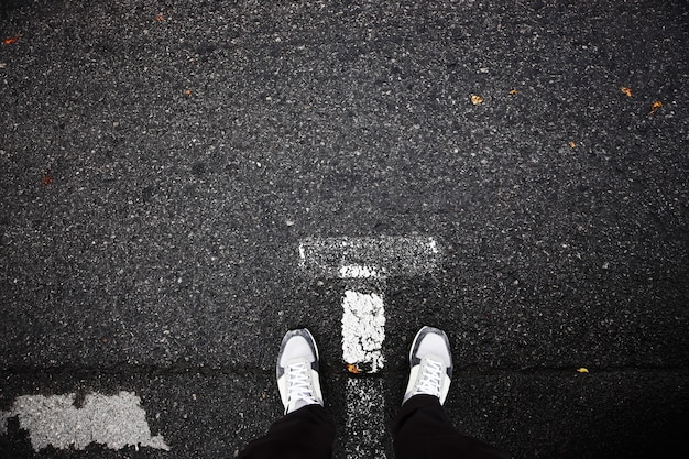 Pov-füße in schuhen auf asphalt.