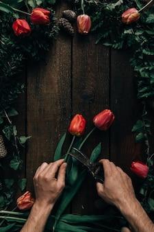 Pov männliche hände, die tulpen auf dunklem holztisch schneiden.
