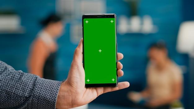 Pov von geschäftsmannhänden, die professionelles smartphone im vertikalen hochformat mit mock-up-grünbildschirm-chroma-key-anzeige halten. freiberufler, der ein isoliertes telefon zum surfen in sozialen netzwerken verwendet