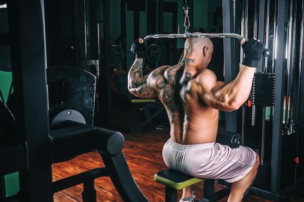 Power athletic guy bodybuilder, führen übung mit fitnessgeräten
