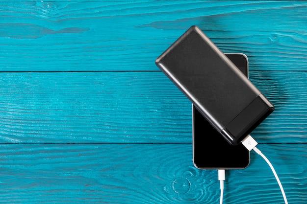 Powerbank lädt den smartphone auf, der auf hölzernem hintergrund lokalisiert wird