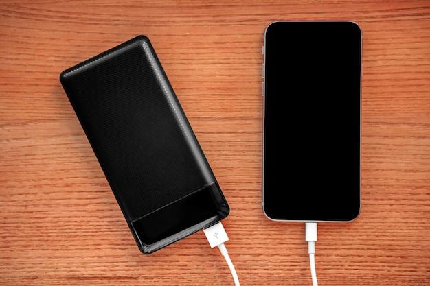 Powerbank lädt den smartphone auf, der auf holz lokalisiert wird