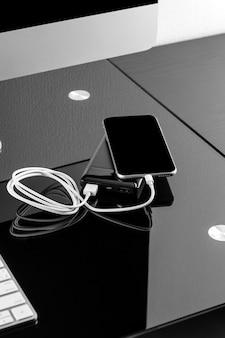 Powerbank lädt den smartphone auf, der auf schwarzem hintergrund lokalisiert wird