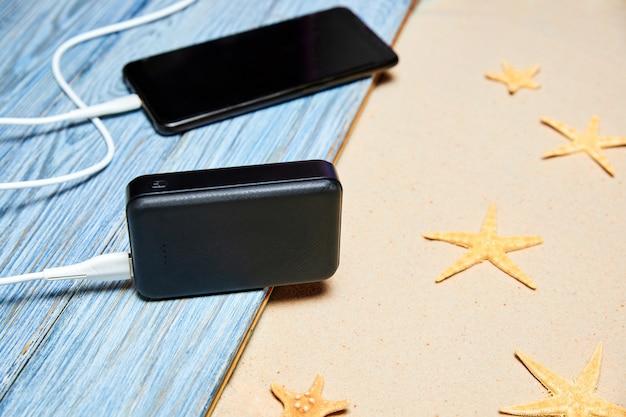 Powerbank lädt ein smartphone auf einem sommerhintergrund aus holzbrettern und sand mit seesternen auf