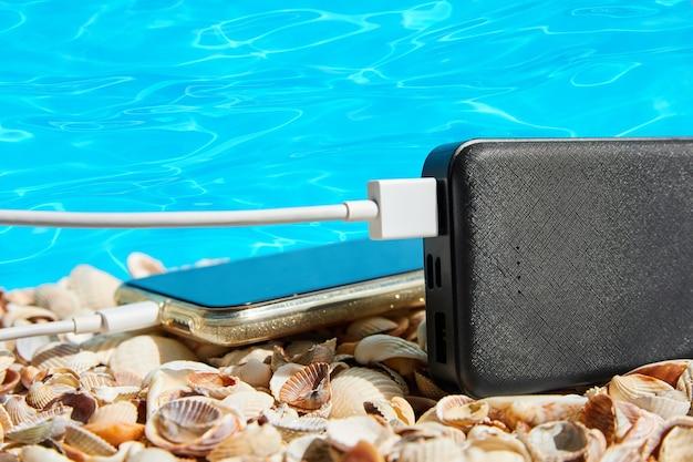Powerbank lädt ein smartphone auf muscheln auf blauem wasserhintergrund auf