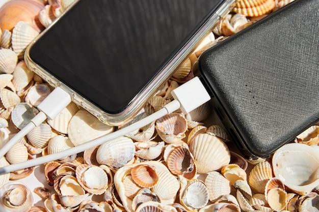 Powerbank lädt ein smartphone auf muscheln